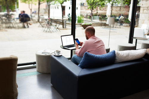 Modern business man busy working on smart phone and laptop computer, young freelancer chatting on cell phone while sitting at sofa of coffee shop, entrepreneur using technology in hotel interior